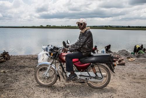 Village de Muchanga, zone d'extraction minière illicite, Kolwezi, province du Katanga, RDC. Le négociant joue le rôle d'intermédiaire entre le creuseur et l'acheteur et/ou la société propriétaire de la zone exploitée illégalement. Il est un des maillons de la chaîne a qui profite modestement le système.