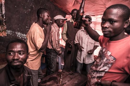 Village de Muchanga, zone d'extraction minière illicite, Kolwezi, province du Katanga, RDC. A la sortie du travail, les creuseurs se retrouvent pour se détendre. La vie sociale s'organise autour des carrières.