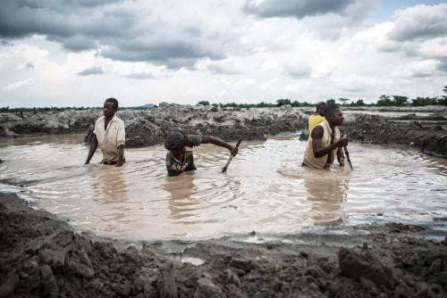 Village de Muchanga, zone d'extraction minière illicite, Kolwezi, province du Katanga, RDC. Dans cette carrière, les creuseurs récupèrent les minerais d'autres sites d'extractions, drainés par la rivière. Ils travaillent toute la journée dans l'eau.