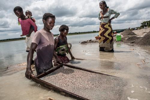 Village de Muchanga, zone d'extraction minière illicite, Kolwezi, province du Katanga, RDC. Une des tâches assignées aux femmes dans la carrière est de laver le minerais brut. Elles trient et tamisent toute la journée dans l'eau du fleuve.